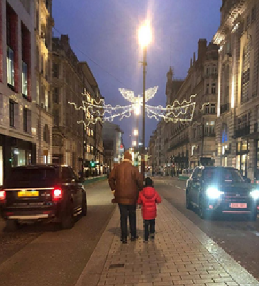 Father and child doing a London Winter walk below the Christmas lights.
